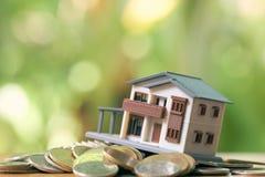 一个式样房子模型在堆被安置硬币 使用作为背景企业概念和房地产概念与拷贝空间为 图库摄影