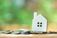 一个式样房子模型在堆被安置硬币 使用作为背景企业概念和房地产概念与拷贝空间为 免版税图库摄影