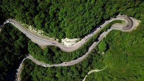 一个弯曲的弯曲道路低谷的鸟瞰图山 股票录像