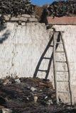 一个弯曲的木楼梯倾斜了对房子,从楼梯,草丛山,一垂直的phot的一个阴影的墙壁 免版税库存图片