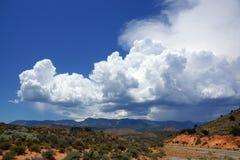 一个弯曲道路通过犹他和蓝色多云天空的一片沙漠 免版税库存图片