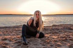 一个强大的黑暗的白肤金发的女孩坐在一个海滩的沙子在黑暗的衣裳带着凝视在晚上日落 免版税库存照片