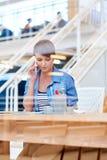 一个当代办公室空间的少妇使用她的电话 库存图片