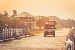 一个徒步旅行队的汽车在日落 通过房子的驱动路的 图库摄影