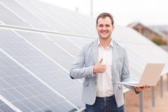 一个微笑的人在太阳电池板附近站立,拿着膝上型计算机并且显示赞许 户外 库存图片