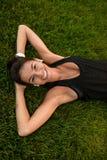 一个微笑的健身女孩的画象修理她的头发的耳机的 免版税库存照片