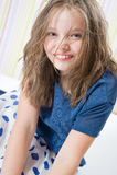 一个微笑的八岁的女孩的画象帽子的 免版税库存图片