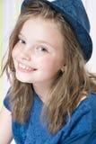 一个微笑的八岁的女孩的画象帽子的 免版税库存照片