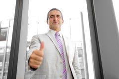 一个微笑的商人的透视图与赞许的 图库摄影