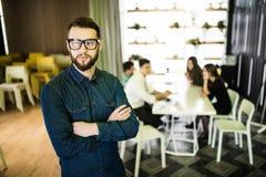 一个微笑的商人的画象与同事的在会议在背景中在办公室 库存照片