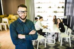 一个微笑的商人的画象与同事的在会议在背景中在办公室 免版税图库摄影