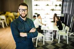 一个微笑的商人的画象与同事的在会议在背景中在办公室 免版税库存照片