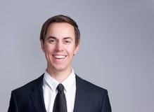 一个微笑的商人的画象在灰色背景隔绝的衣服的 图库摄影