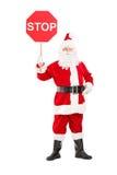 一个微笑的圣诞老人藏品停车牌的全长画象 免版税库存照片