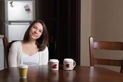 一个微笑的女孩是在桌上 库存照片