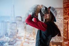 一个微笑的女孩由面孔拿着一只猫 免版税库存图片