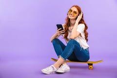 一个微笑的女孩的全长画象太阳镜的 免版税图库摄影