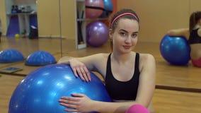 一个微笑的女孩的特写镜头画象有一个球的健身的 股票录像