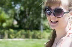 一个微笑的女孩的画象太阳镜的 免版税库存照片