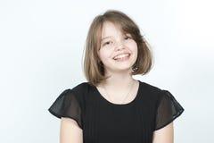 一个微笑的女孩的画象一件黑女衬衫的 库存照片