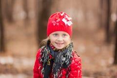 一个微笑的女孩的画象在步行的一个春日在森林 免版税库存图片