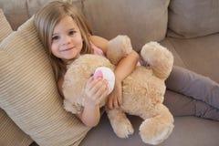 一个微笑的女孩的画象有被充塞的玩具的坐沙发 免版税库存图片