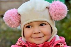 一个微笑的女婴的画象一个桃红色帽子的 免版税库存图片