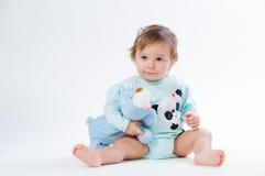 一个微笑的孩子的画象有一头玩具熊的,在白色背景 免版税库存照片