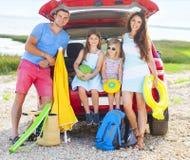 一个微笑的家庭的画象有两个孩子的海滩的 免版税图库摄影