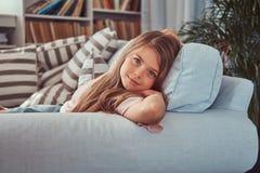 一个微笑的小女孩的画象有长的棕色头发的和穿甲扫视,在家说谎在沙发 免版税库存照片