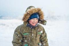 一个微笑的小男孩的画象有落的雪的 库存图片