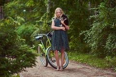 一个微笑的小白肤金发的女孩的充分的身体画象一件便服的,举行逗人喜爱的波美丝毛狗狗 在一辆自行车的乘驾在 免版税图库摄影