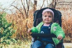 一个微笑的小婴孩的画象有蓝眼睛的在一件桃红色帽子和高尔夫球外套 图库摄影