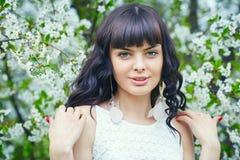 一个微笑的少妇的美丽的面孔反对一棵开花的树的在一个晴天 免版税库存照片