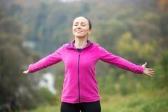 一个微笑的少妇的画象户外在运动服 免版税图库摄影