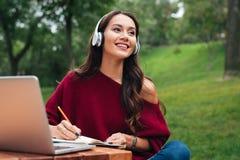 一个微笑的年轻亚裔女孩的画象耳机的 免版税库存图片