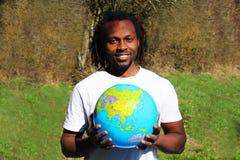 一个微笑的年轻人在他的手上拿着世界地球 库存照片