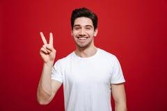 一个微笑的年轻人的画象白色T恤杉的 免版税库存照片