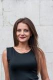 一个微笑的愉快的典雅的少妇的画象站立反对蓝色墙壁背景的黑礼服的 免版税库存照片