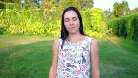 一个微笑的浅黑肤色的男人的画象有起波纹的面颊的反对一个绿色公园 美丽的少妇在公园站立并且看 股票视频