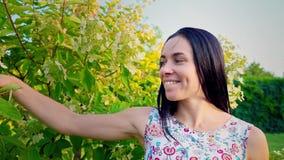 一个微笑的浅黑肤色的男人的画象有起波纹的面颊的反对一个绿色公园 美丽的少妇在公园站立并且看 股票录像