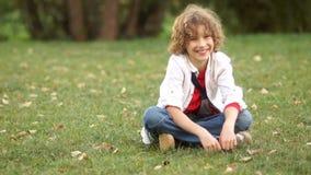 一个微笑的男孩坐绿草在夏天公园 一位男小学生在度假,穿白色衬衫,一件红色T恤杉 股票视频