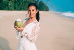 一个微笑的美丽的女孩喝在一个椰子的一个鸡尾酒在一个含沙空的空的海滩 模型发光并且微笑 免版税库存照片