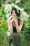 一个微笑的美丽的女孩的画象花圈花和草本的在草甸晴天 年轻斯拉夫的妇女 免版税库存图片
