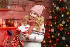 一个微笑的逗人喜爱的妇女开头礼物盒的画象由圣诞树的 免版税图库摄影