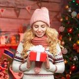 一个微笑的逗人喜爱的妇女开头礼物盒的画象由圣诞树的 免版税库存图片
