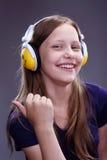 一个微笑的青少年的女孩的特写镜头画象有耳机的 库存图片