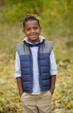 一个微笑的非裔美国人的年轻男孩的逗人喜爱的室外画象 库存图片