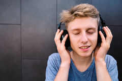一个微笑的年轻人的画象有他的注视闭合,享受听到在他的耳机的音乐 图库摄影