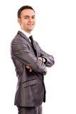 一个微笑的年轻商人的画象与被交叉的双臂的 免版税库存照片